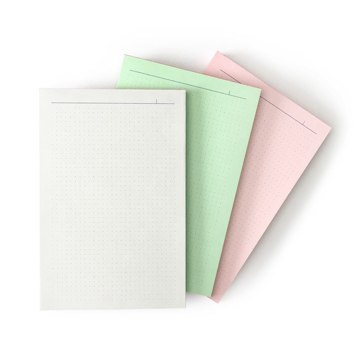 array of risograph printed notepads in gray, green and pink with navy blue dot pattern